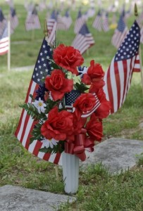 Vase with Flowers and USA Flags Decorating Military Grave