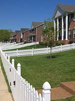 Tract Home Neighborhood with Turf Grass Lawns and White Picket Fences