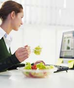Woman Eating a Salad for Lunch at Her Desk