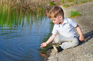 Boy Sitting Next to Lake with Water Pouring Through Hand