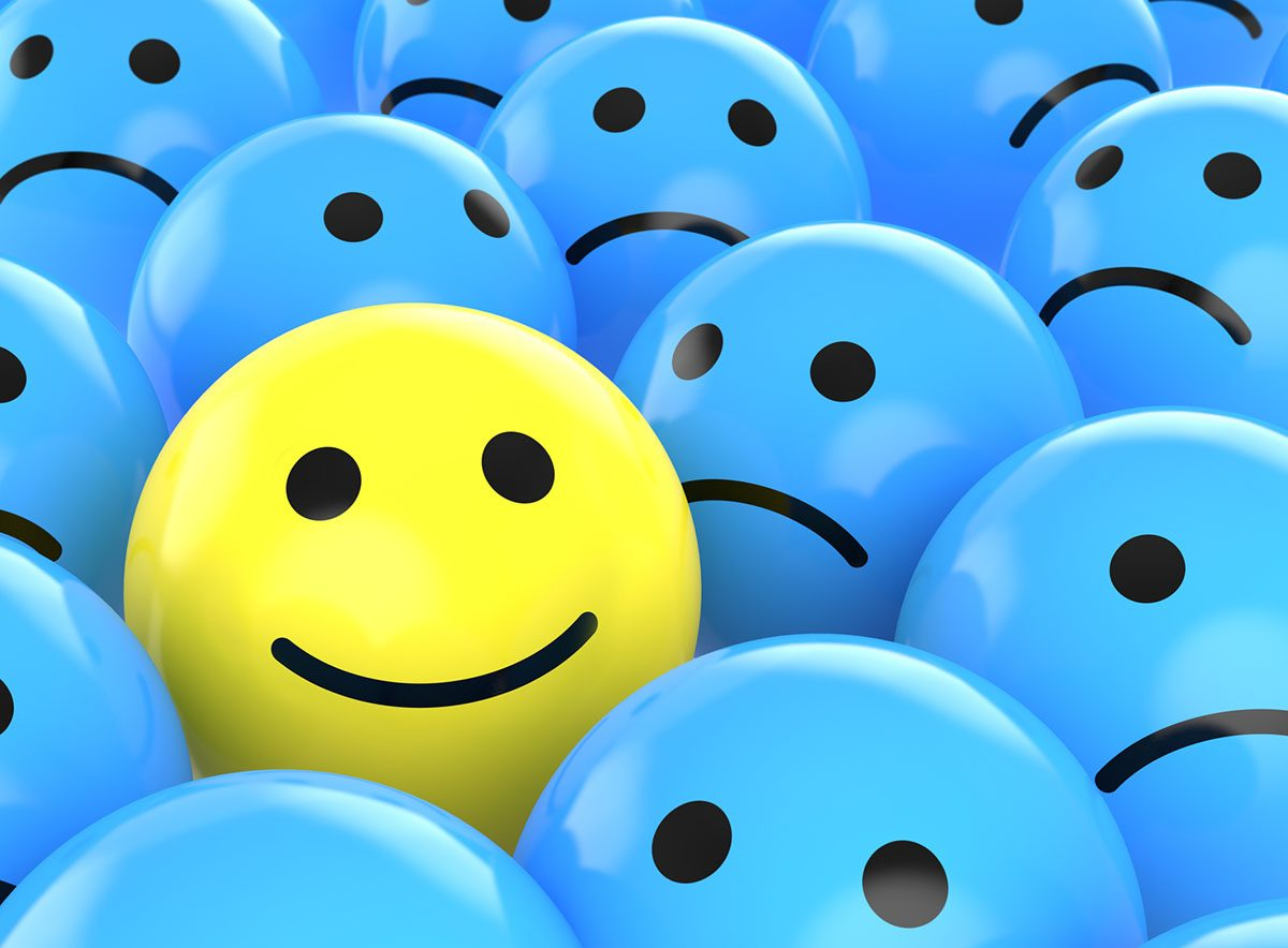 Yellow Happy Face Ball Surrounded by Blue Sad Face Balls