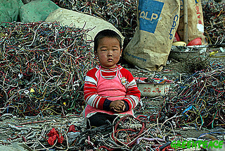 Child sitting among toxic e-waste