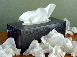 Box of Paper Facial Tissues with Pile of Used Tissues
