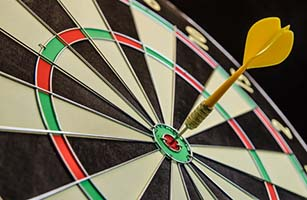 Goal Completion - Dart Board with Dart in Bullseye