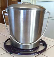 Unlikely Composter's One-Gallon Stainless Steel Compost Pail with Lid on Trivet on Kitchen Counter