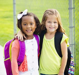 Two Young Girls with Backpacks Standing at School
