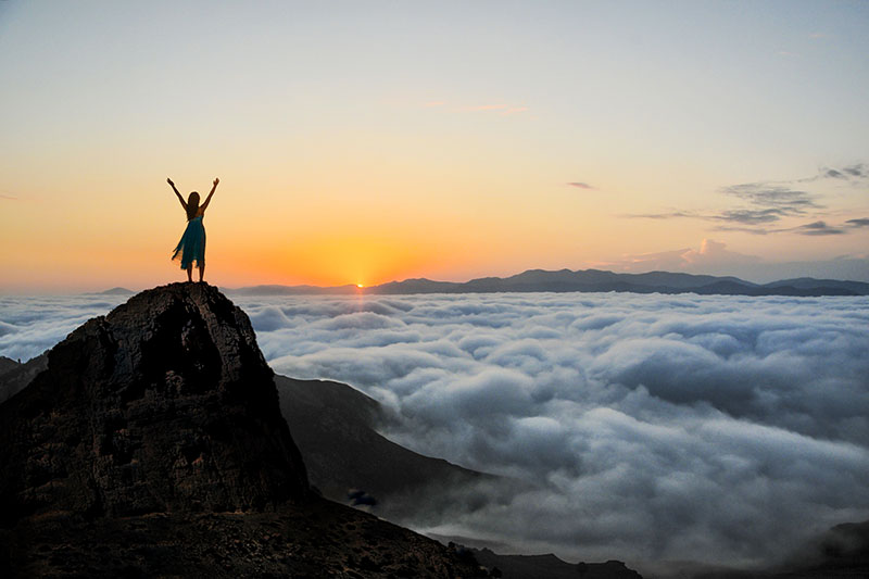 Empowerment - Woman with Outstretched Arms Standing on Mountaintop with Clouds at Sunset