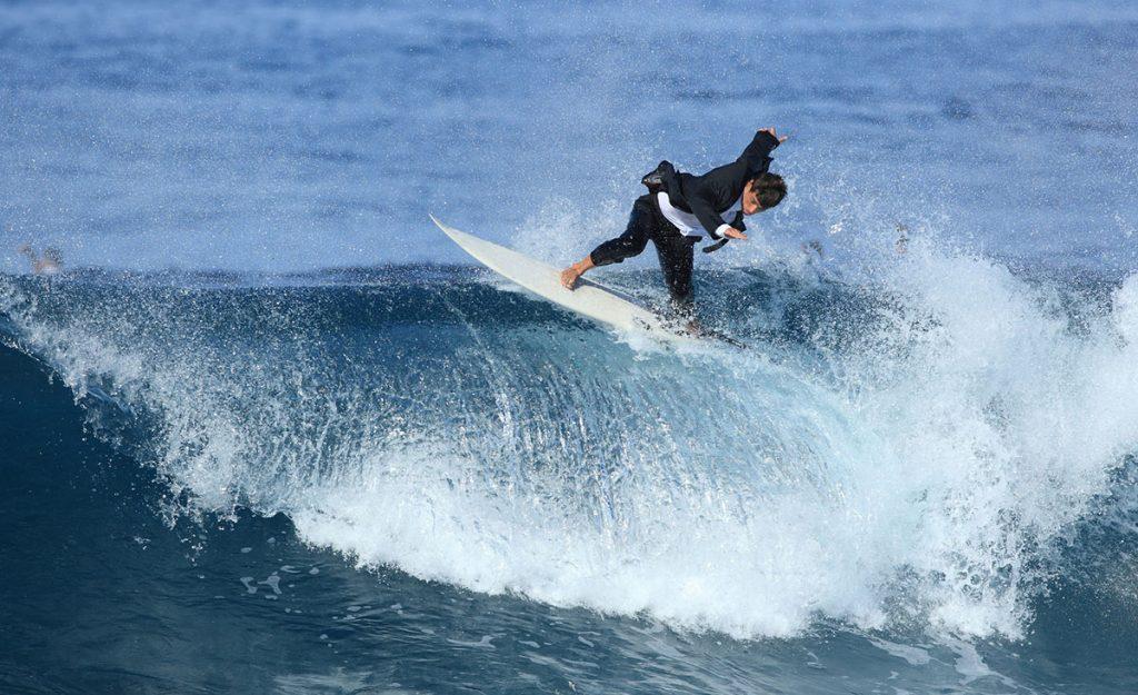 Businessman Surfing a Wave in Ocean