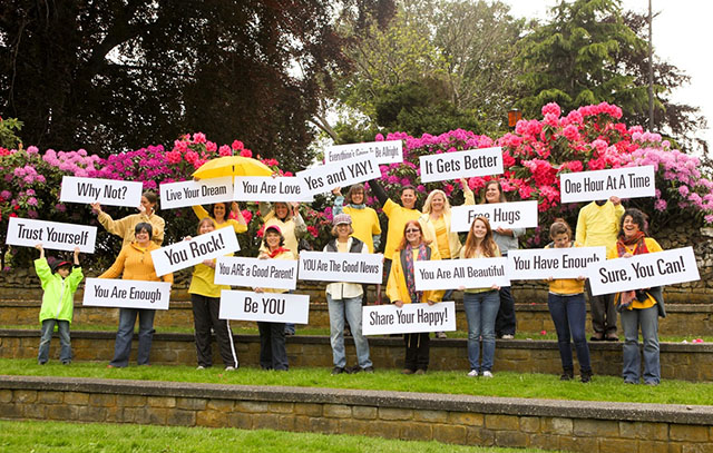 People Wearing Yellow and Holding Encouraging Signs - Happiness Sprinkling Project