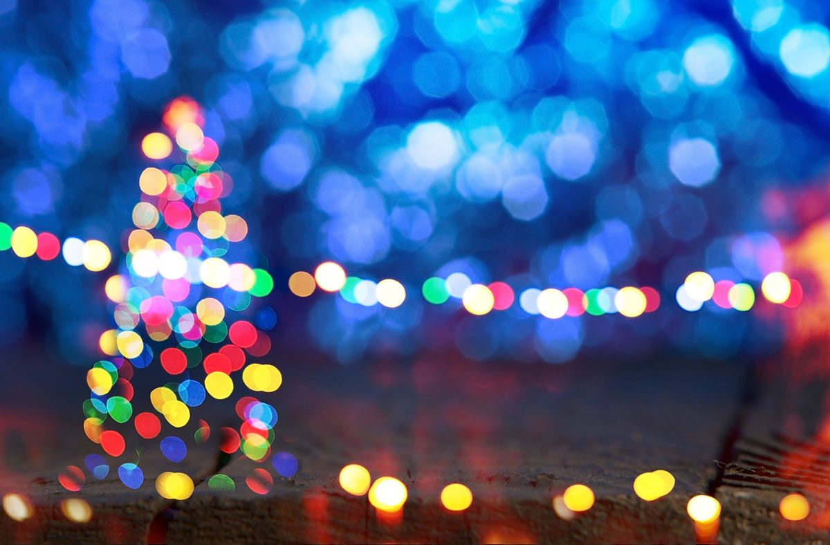 Out of Focus Colored Christmas Lights against a Blue Background