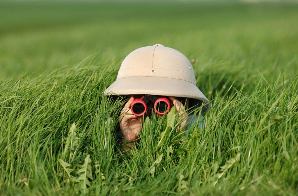 Little Kid Wearing Pith Helmet Lying in Grass Looking through Binoculars