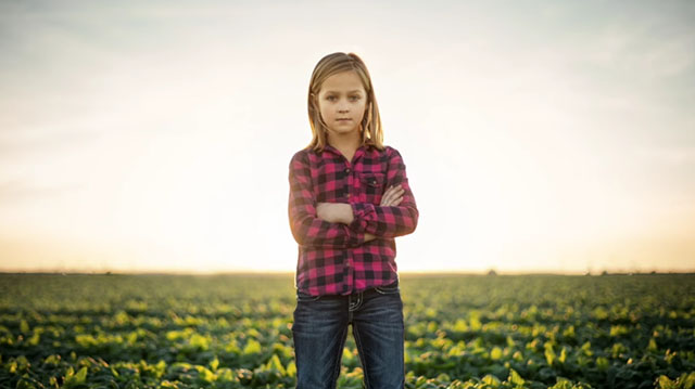 Young Female Farmer Standing in an Agricultural Field