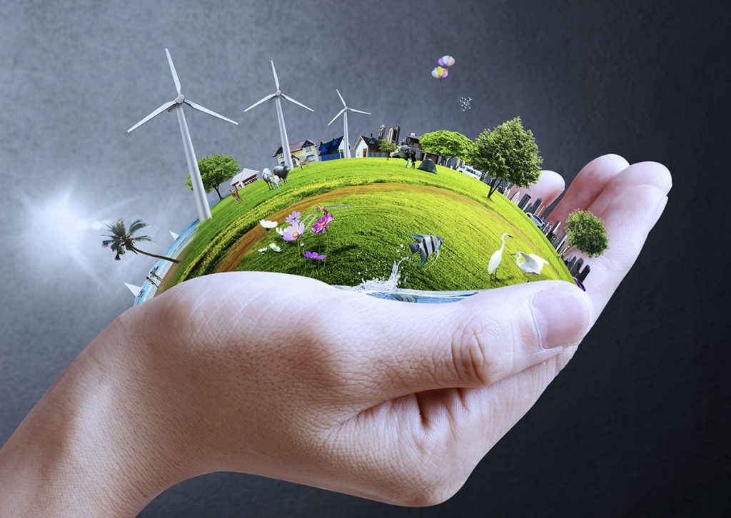 A Hand Holding a Tiny City Powered by Renewable Energy