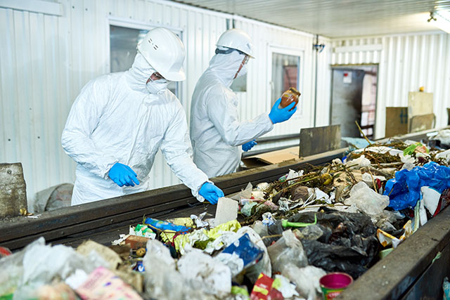 One of Two Workers Sorting Recycling Holds a Half Full Glass Jar
