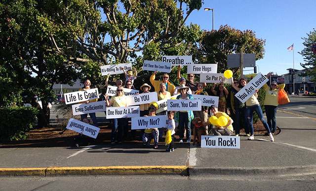 People Wearing Yellow Standing on Street Corner Holding Happiness Sprinkling Signs