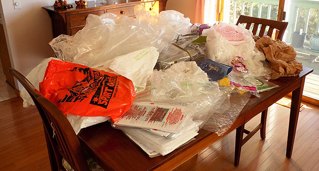 Pile of Single-Use Plastic Bags and Packaging on Dining Room Table