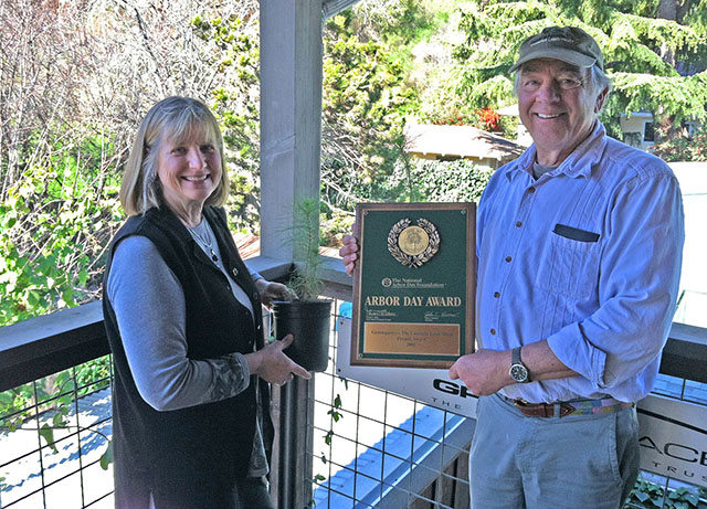 Mary Webb and Rick Hawley Holding Greenspace 2001 Arbor Day Foundation Award and Two Monterey Pine Seedlings