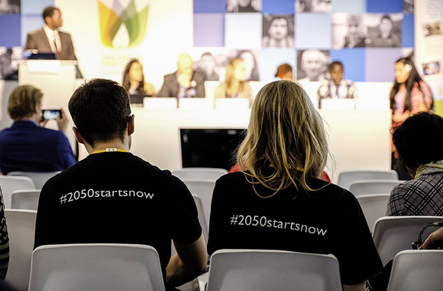 Attendees Wearing T-Shirts with Hashtag 2050startsnow at 2015 UN COP 21 Climate Conference in Paris, France