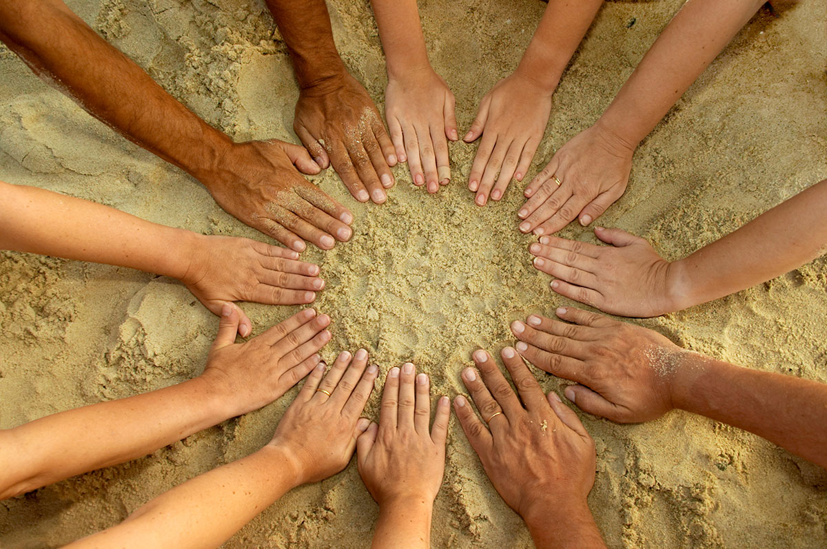 Circle of Hands Resting on Sand