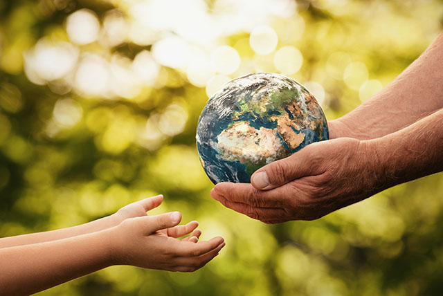 Adult Handing an Earth Globe to a Child