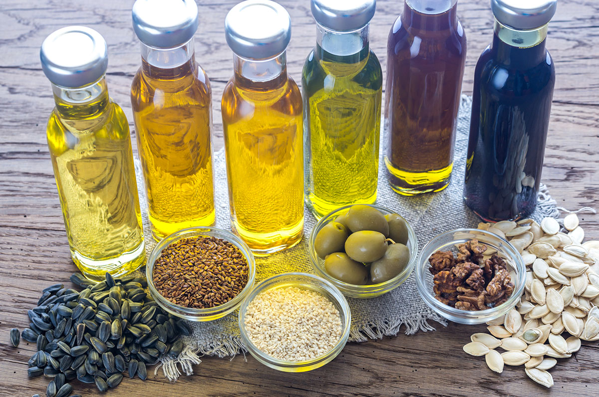 Bottles of Six Plant-Derived Cooking Oils with Seeds, Fruits, and Nuts